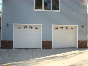 Stone veneer wainscoting panels are trimmed with a regular wood saw to fit around these garage doors.