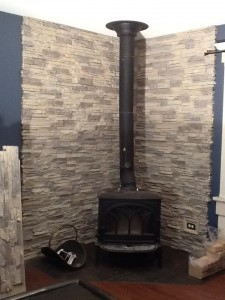 Wood stove backing built with stacked stone style, fire-rated panels
