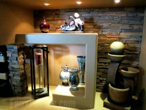 Recessed lighting and drystack stone style panels added to a fireplace shelving unit.