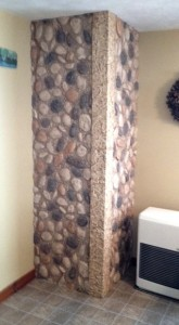 Corner unit covered in river rock style panels as part of a small bathroom remode.