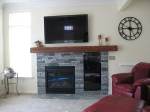 A ledgestone fireplace surround built with veneer panels and a fake wood mantel.