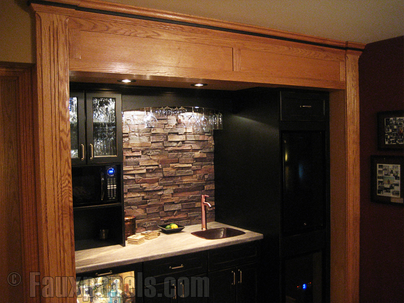 Stone look backsplash installed behind a mini kitchen bar area.