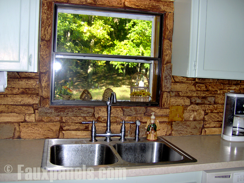 Stone look backsplash behind a kitchen sink.