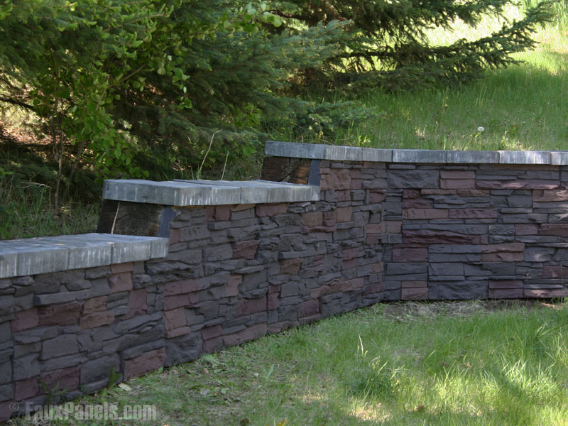 A graduating retaining wall outfitted with artificial stacked stone paneling.