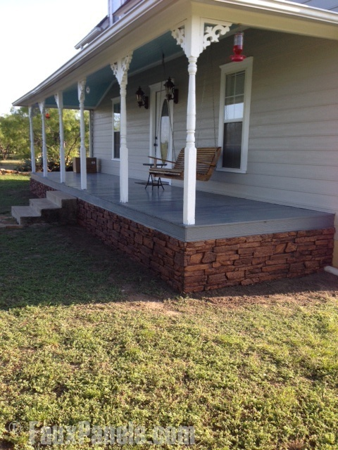 A residential front porch with brown faux stacked stone panels placed in the gap area.