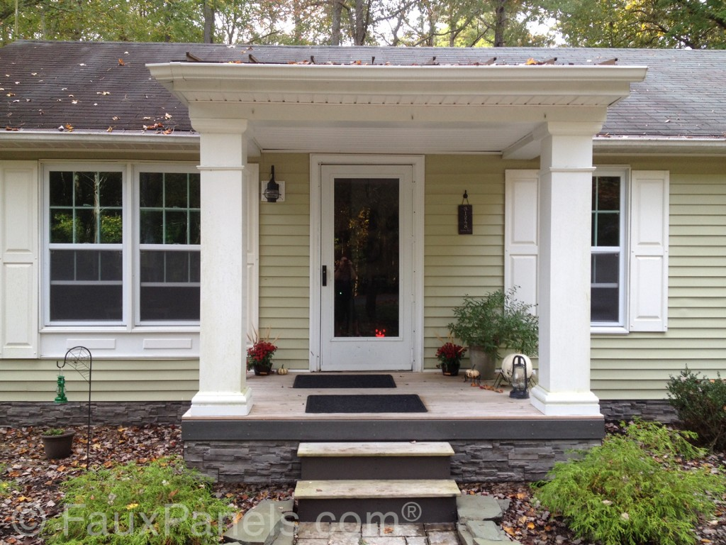 A home's front porch is accented with faux stone siding installed on the foundation.