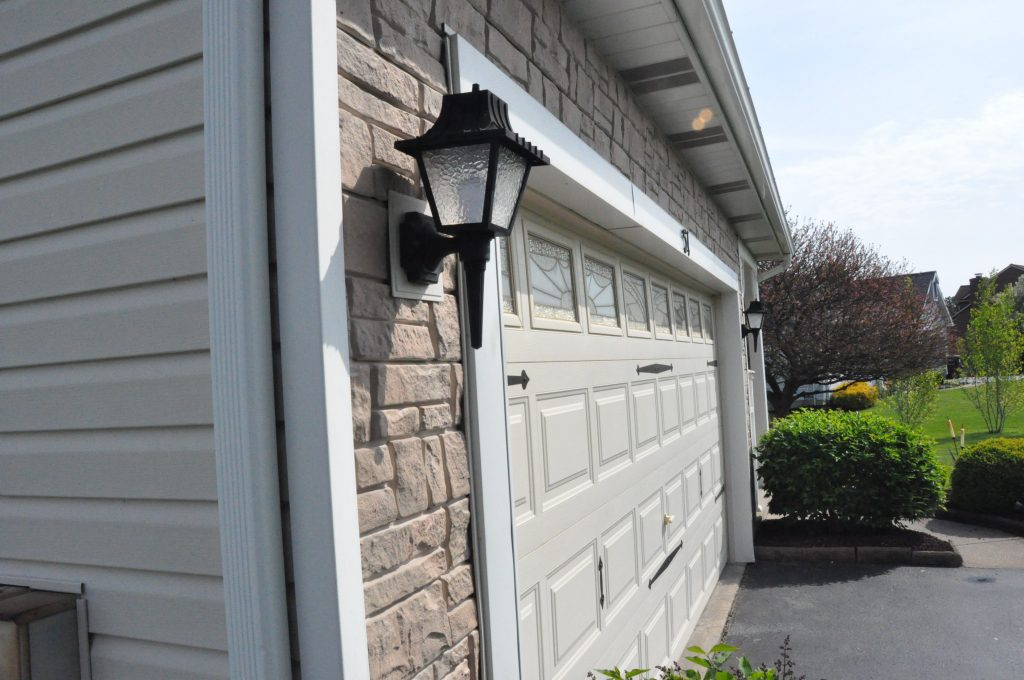 This picture demonstrates the dramatic contrast between regular vinyl siding and faux rock siding.