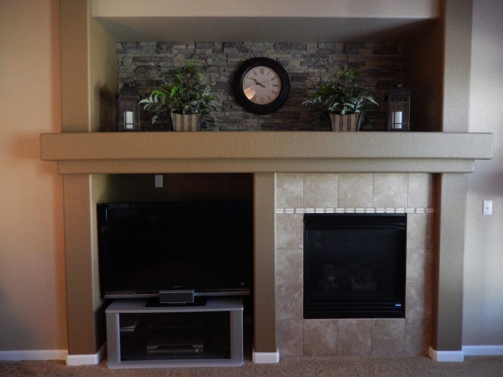 Family room alcove with stacked stone panels accenting the upper shelf wall.