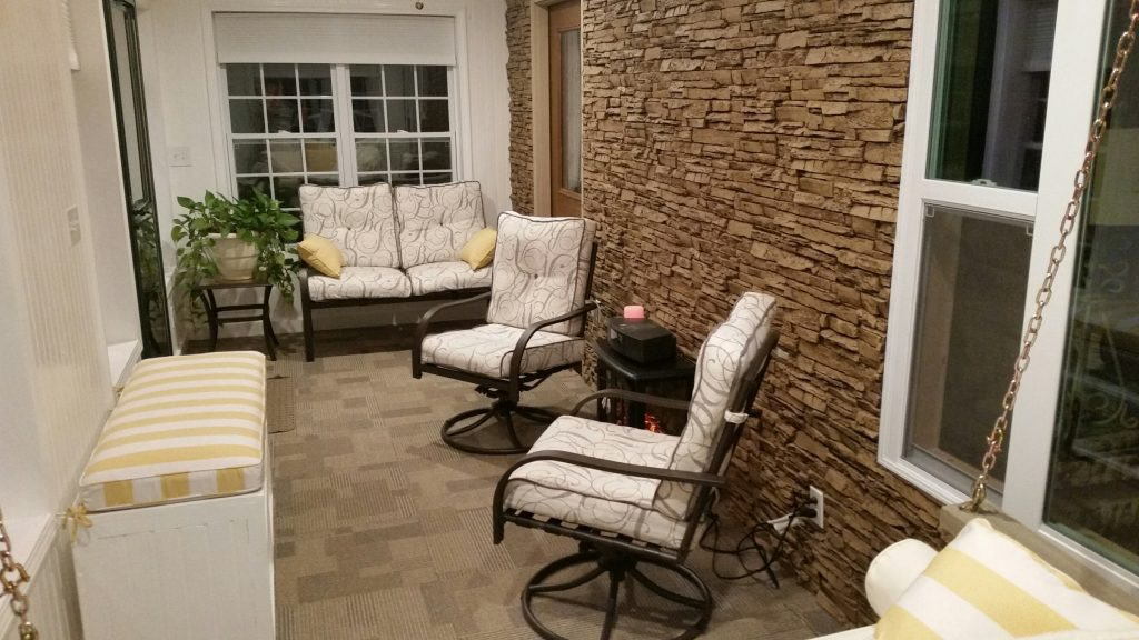 A home's porch converted into an enclosed sunroom with new patio-style furniture, rug and a stacked stone accent wall.