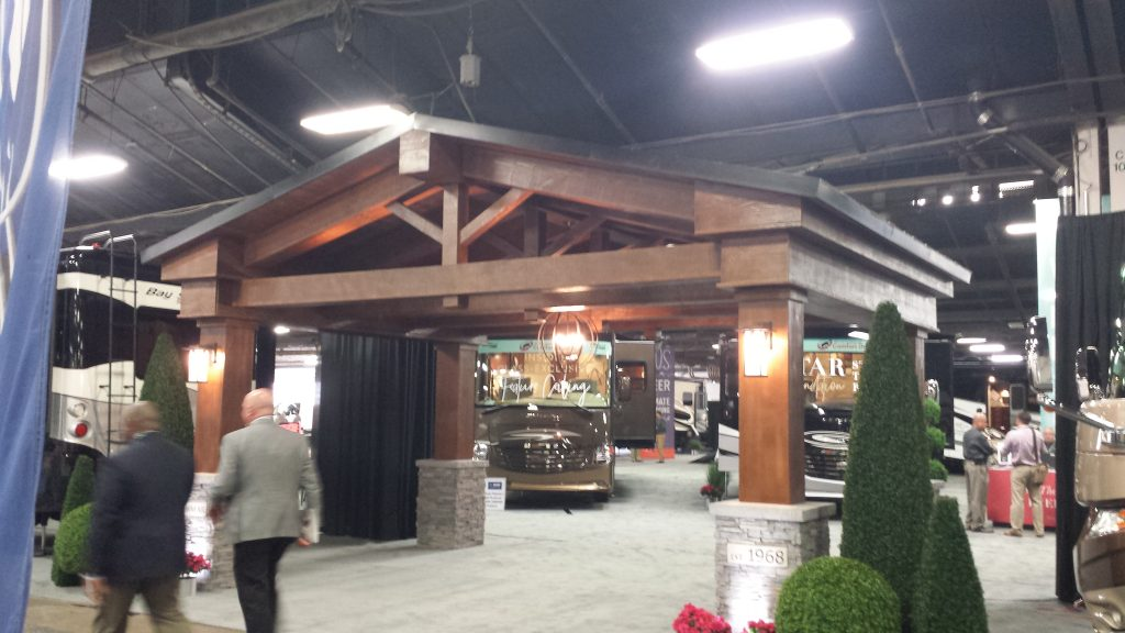 The Newmar Corporation's creative exhibition booth design featured faux stone column wraps at the 4 corners of the display.
