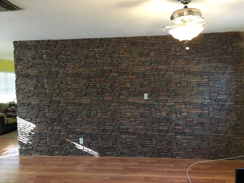 Completed accent wall made with stacked stone panels and matching wall corner trim.