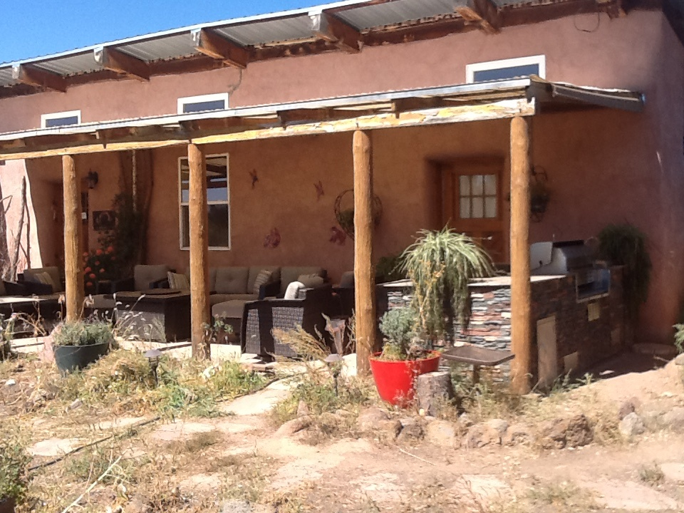 Patio of southwestern style home with new outdoor kitchen including BBQ island with a faux stone finish.