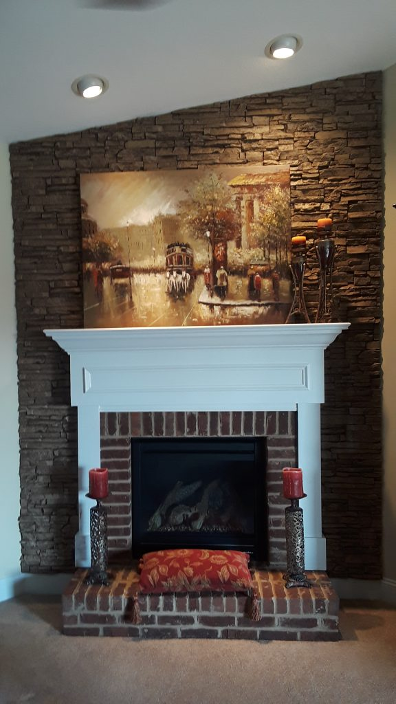 Fireplace backdrop created with stacked stone style panels in Taffy Beige color.