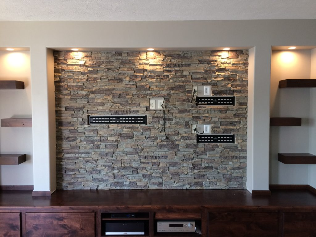 Media center finished with stone style wall panels with holes cut out to accommodate mounting brackets.