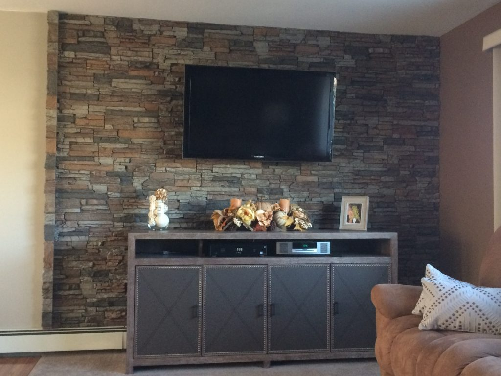 A living room's accent wall created with stacked stone panels behind the TV.