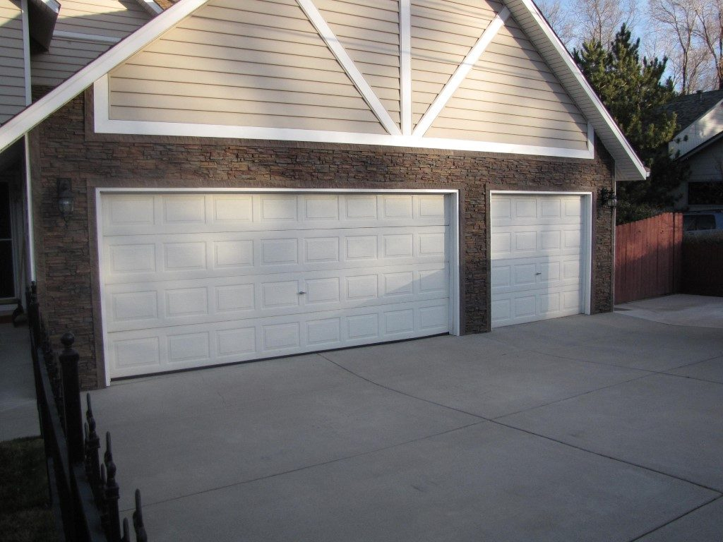 Garage exterior remodel using Regency Stacked Stone panels in Earth color and matching door trim.