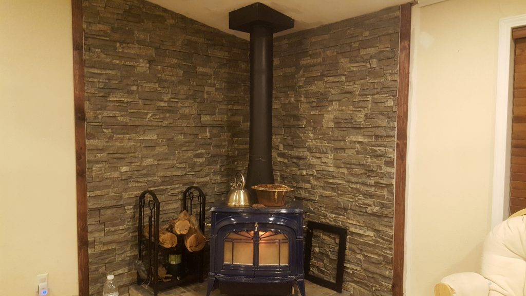 Wall behind a wood stove created with stacked stone style panels.