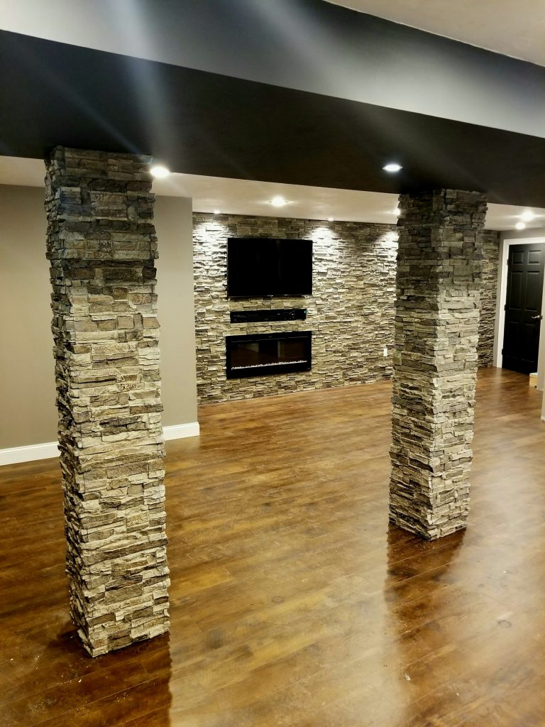 New basement accent wall with TV and fireplace and lally columns covered in Norwich Stacked Stone panels and matching column wraps.