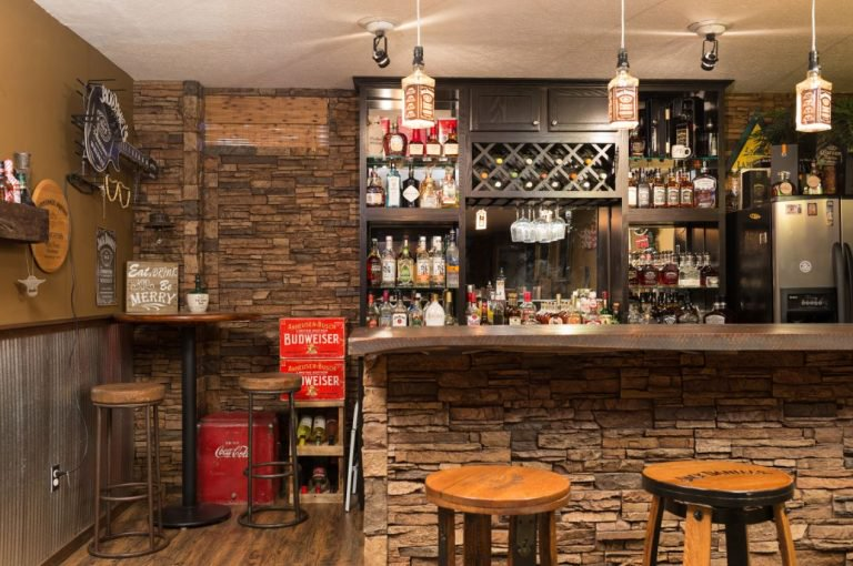 Basement bar front and surrounding walls covered in Norwich Stacked Stone.
