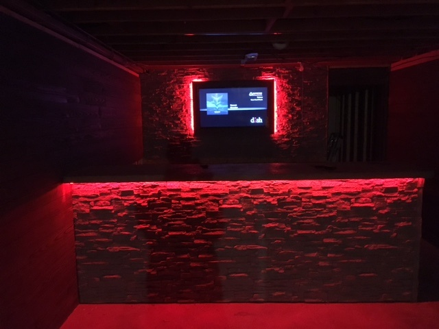 Norwich Stacked Stone panels in Frosted Gray and color-changing LED lights made for a stunning home cinema and bar in a man cave.