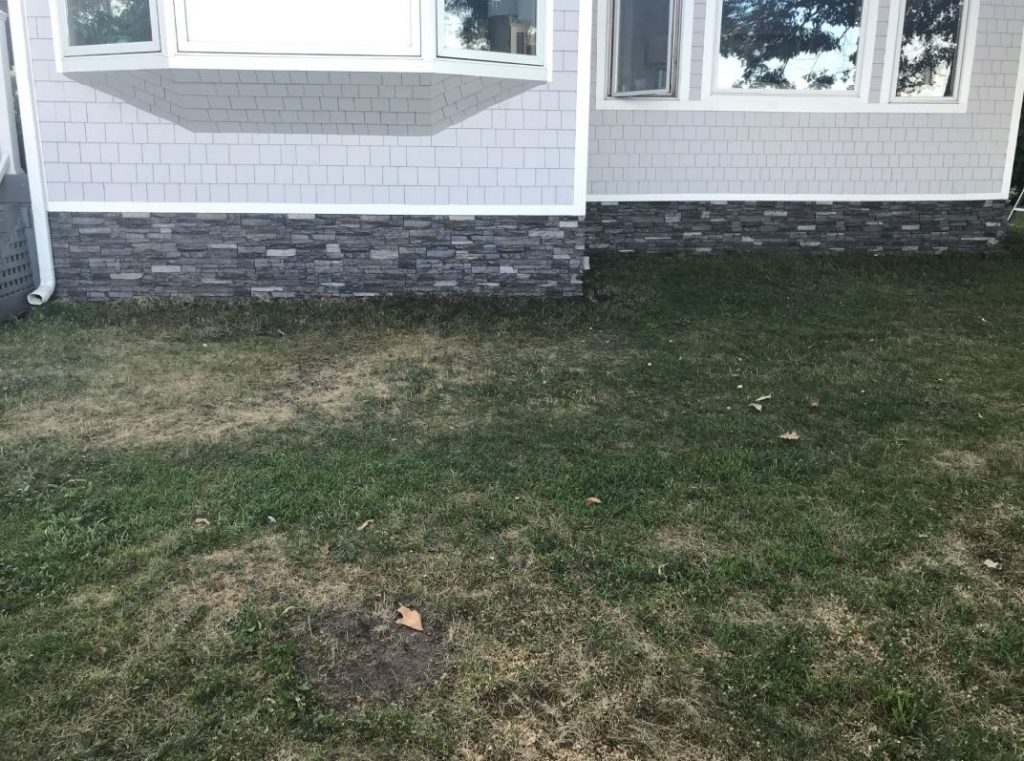 DIY mobile home remodel with stacked stone style panels installed as skirting.