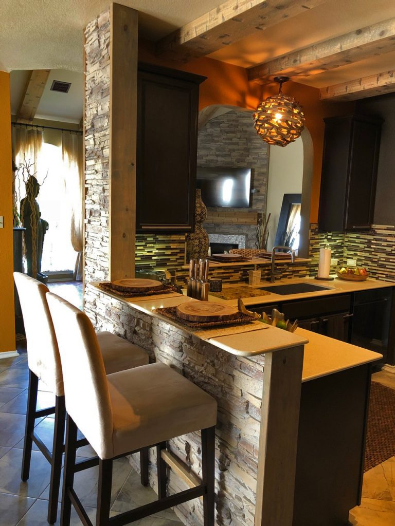 Kitchen bar design using stacked stone panels on the exterior surface.