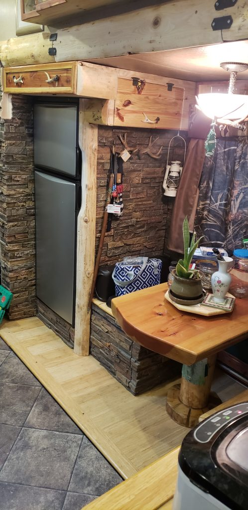 An RV's interior design with a rustic hunting lodge theme using Dry Stack stone panels.