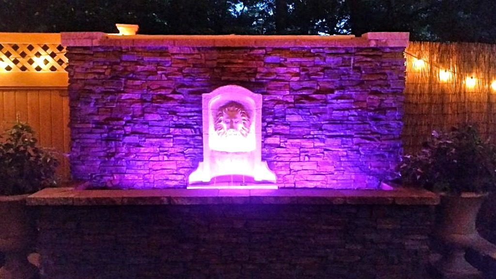 Outdoor water wall with stacked stone style finish is lit up at night with color-changing LED lights.