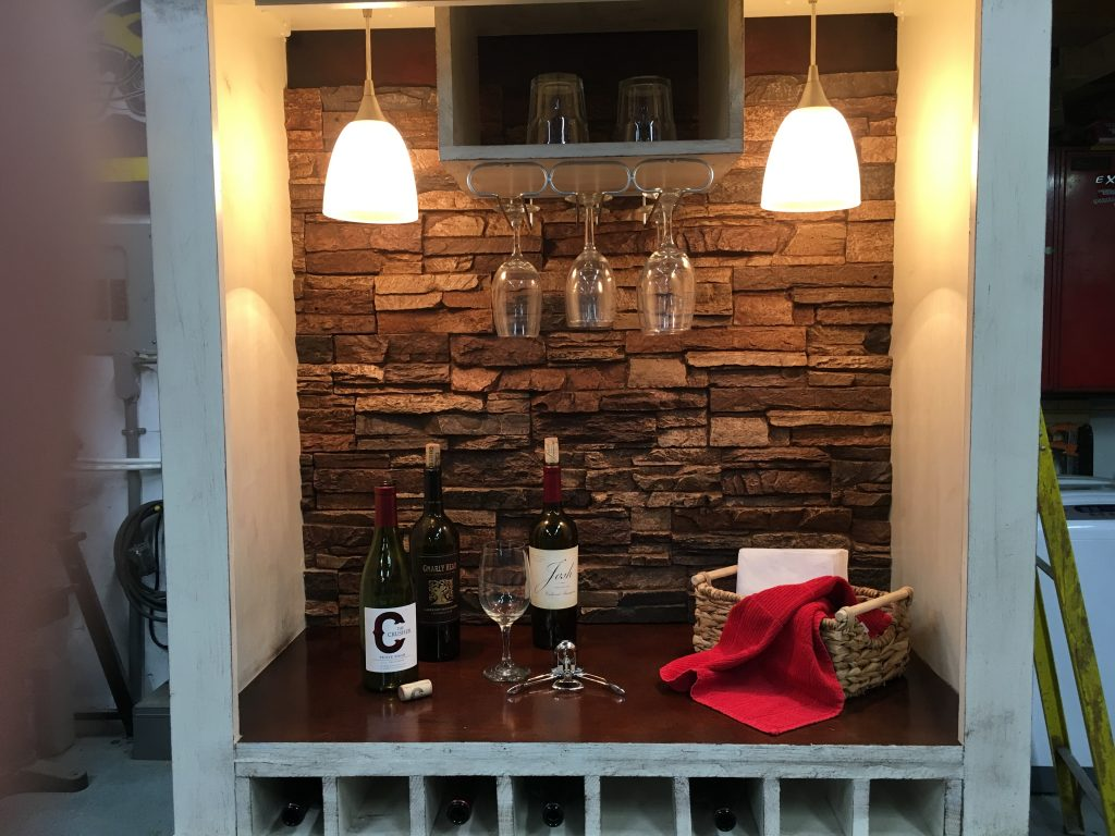 Bar cabinet built from an old TV armoire with wine racks, brushed nickle lights and faux stone panels.