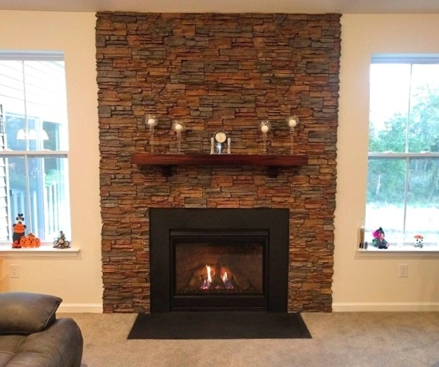 Fireplace wall design with stacked stone finish.