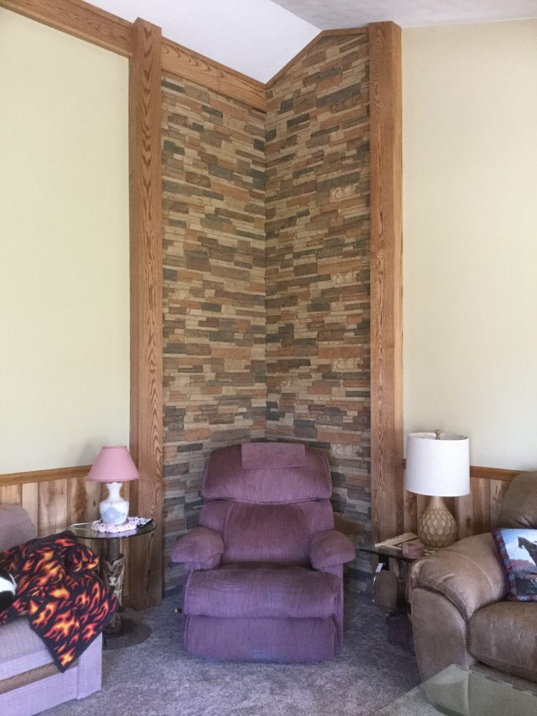 Living room wall corner accented with drystack stone-style panels.