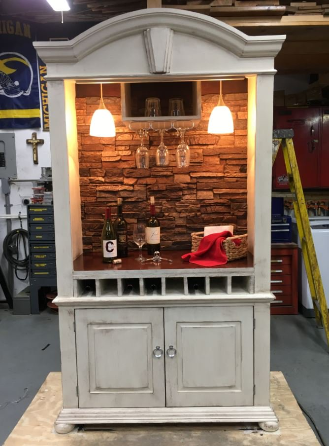 Armoire re-purposed as a bar cabinet with a stone-style back wall.