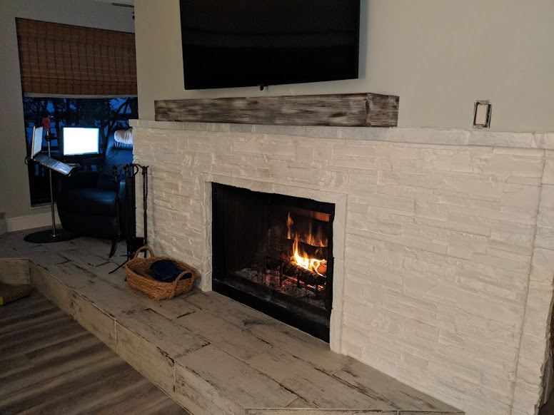 Faux white stone panels create a fireplace surround, fitting in with the home's beachy decor.