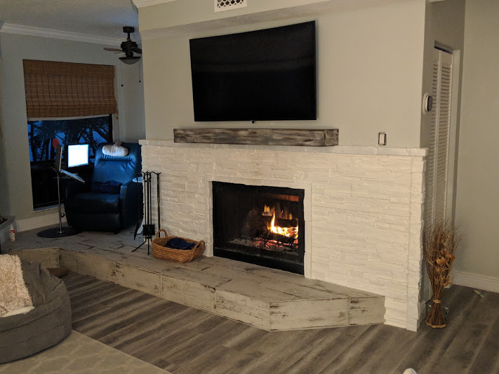 Fireplace updated with a faux white stone surround.