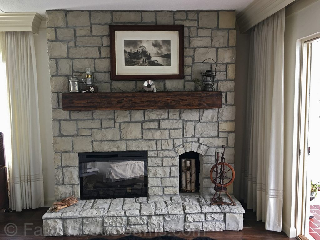Large rock fireplace with a Custom Timber mantel.