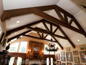 Decorative wooden trusses in a living room with corbels attached to the ends.