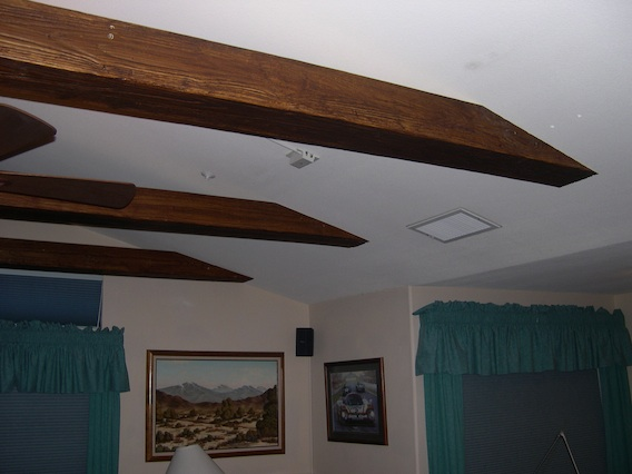 Sloped Ceiling with faux beams cut to match the angle and fit flush