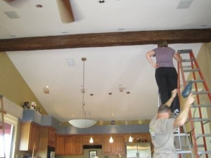 Fake wood timber beam being installed in a kitchen