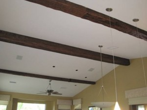 Rubber mounting straps cover the join between two fake wood timber beams.