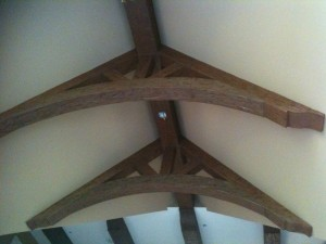 Through the use of faux wood arched beams, this elegant design was put up in far less time and for far less money than if done with real wood.