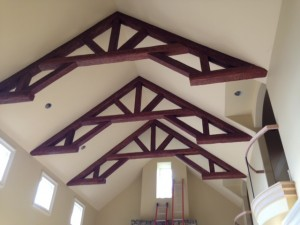 Ornate king post trusses made from faux wood installed on a cathedral ceiling.