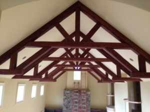 Decorative king post trusses on a home's cathedral ceiling.
