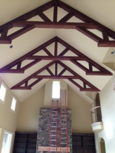 Cathedral ceiling with elaborate king post trusses made from faux Timber beams.
