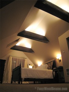 Bedroom ceiling beams with upward facing lights for a soft glow.