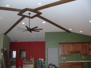 Faux beams were cut and arranged in an interesting pattern to highlight the ceiling fan.