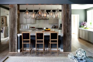 A new home's kitchen featuring reclaimed wood columns flanking the island and large hanging globe lights.