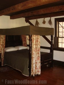 Historic home's remodeled bedroom with faux beams lending an authentic real wood look.