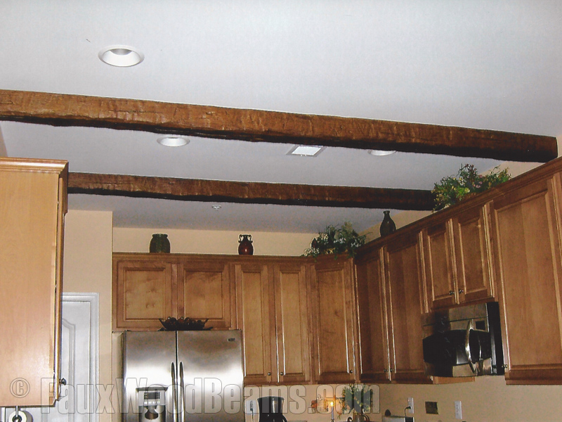 Heavily distressed timber beams installed on a kitchen ceiling.