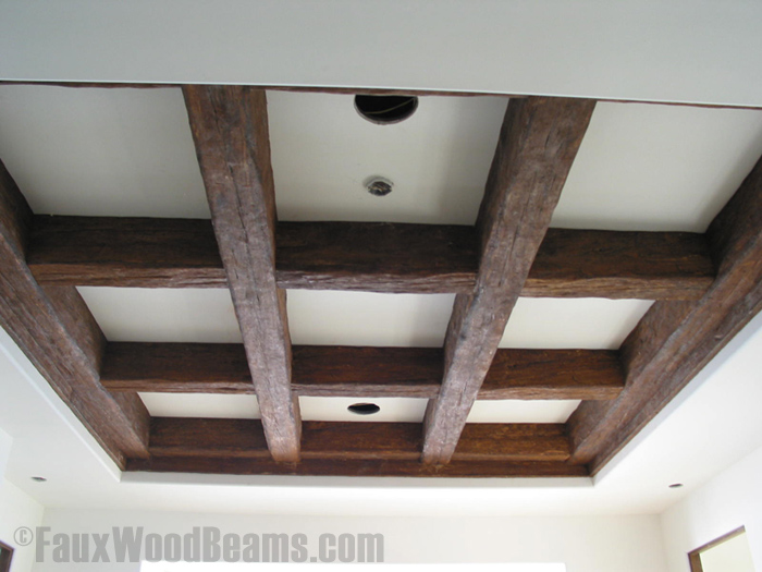 Tray ceiling with beams arranged in a coffered design, using beams with an authentic distressed wood look.