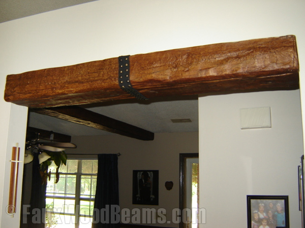 Custom Timber beam with decorative strap accents an entranceway.